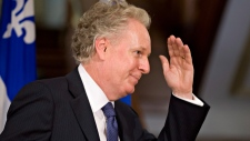 Quebec Liberal Party Leader Jean Charest waves goodbye after he announced he resignation at the Queb