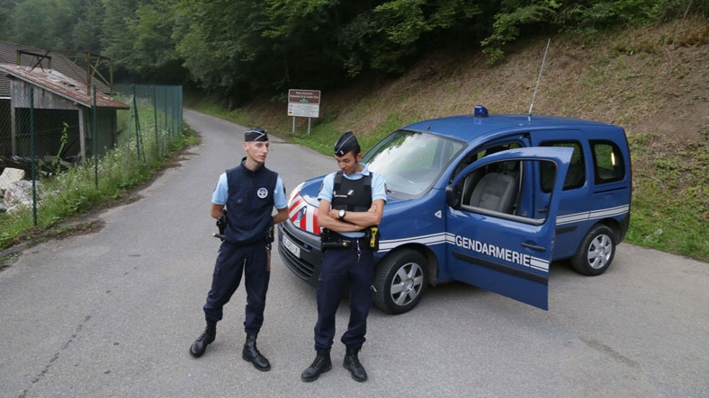 Gendarmes block access to a killing site near Chevaline, French Alps, Wednesday Sept. 5, 2012. French authorities say at least four people have been shot to death in a forest in the Alps. An official with the regional administration for the Haute-Savoie region says three of the bodies were found in a BMW registered in Britain. (AP / Alexis Moro)