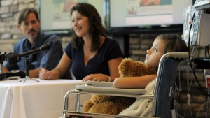 Seven-year-old Sierra Jane Downing from Pagosa Springs, Colo., looks on while her father Sean Downing and mother Darcy Downing talk about her recovery from Bubonic Plague at the Rocky Mountain Hospital for Children at Presbyterian/St. Luke's during a news conference Wednesday, Sept. 5, 2012, in Denver.  (AP Photo/Jack Dempsey)