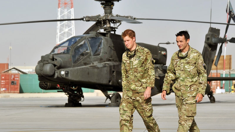 Prince Harry is shown the Apache flight-line Friday, Sept. 7 2012 by a member of his squadron (name not provided) at Camp Bastion in Afghanistan, where he will be operating from during his tour of duty as a co-pilot gunner. (AP / John Stillwell, Pool)