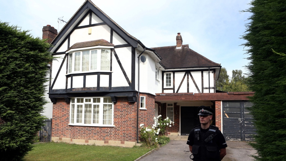 Police stand outside the home of Saad al-Hilli in Claygate, Surrey, who has been named by French media as one of the members of a British family who was shot dead by a gunman in the French Alps, Thursday Sept. 6, 2012 . (AP / Steve Parsons/PA)