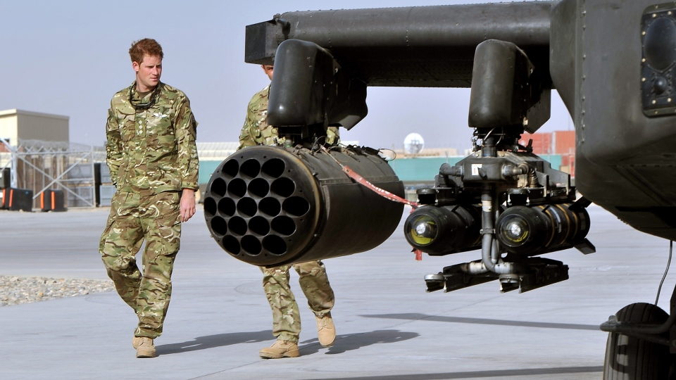 Prince Harry, left, is shown the Apache helicopter by a member of his squadron (name not provided) at Camp Bastion in Afghanistan, Friday, Sept. 7, 2012. (AP / John Stillwell)