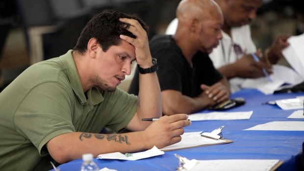 In this Tuesday, Aug. 21, 2012, file photo, job seekers fill out applications at a construction job fair in New York. (AP / Seth Wenig, File)