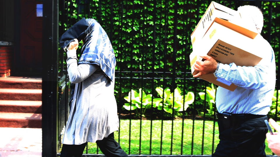 A woman and a man shield their faces as they make their way into the Iranian embassy in Ottawa on Friday, Sept. 7, 2012. (Fred Chartrand / THE CANADIAN PRESS)