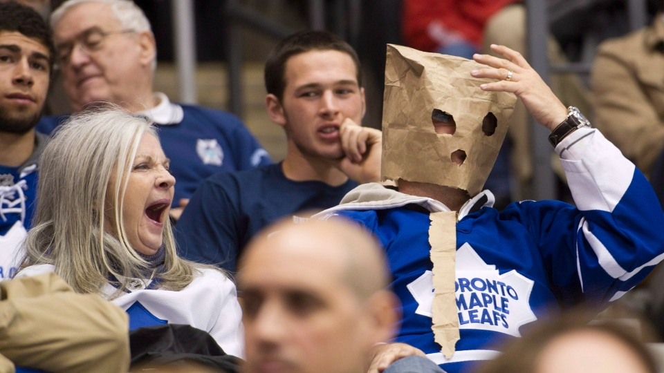 A women yawns, left, as a Toronto Maple Leafs fan wears a paper bag on his head as the Maple Leafs play against the Tampa Bay Lightning during second period NHL hockey action in Toronto on Thursday, April 5, 2012. Nathan Denette / THE CANADIAN PRESS