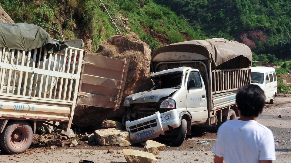 A man looks at the trucks damaged by fallen rocks after an earthquake in Zhaotong town, Yiliang County, southwest China's Yunnan Province, Friday, Sept. 7, 2012. (AP Photo)