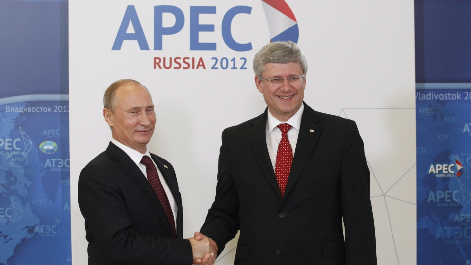 Prime Minister Stephen Harper shakes hands with Russian President Vladimir Putin as he arrives for the official welcome at the APEC Summit in Vladivostok, Russia on Saturday, Sept. 8, 2012. (Adrian Wyld / THE CANADIAN PRESS)