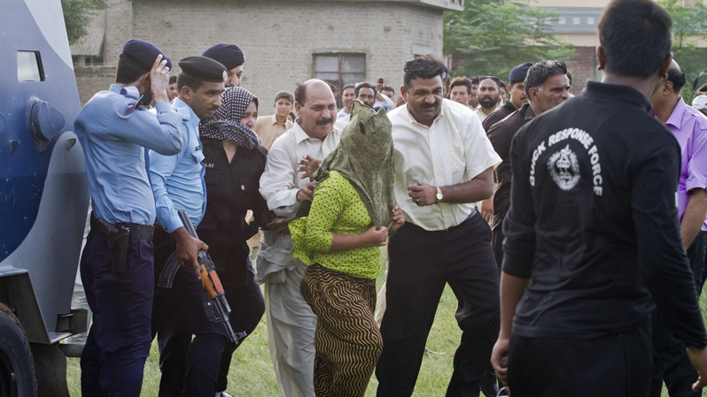 Pakistani police officials escort a young Christian girl, center, accused of blasphemy for allegedly burning pages of a Quran, toward a helicopter following her release from central prison on the outskirts of Rawalpindi, Pakistan, Saturday, Sept. 8, 2012. (AP / Anjum Naveed)