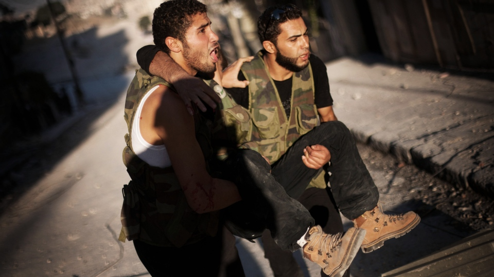 Two Free Syrian Army fighters help a wounded comrade during fighting in the in Izaa district of Aleppo, Syria on Friday, Sept. 7, 2012. (AP /Manu Brabo)