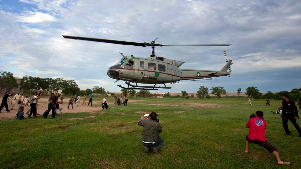 Pakistani cameramen film a helicopter takes off, carrying a young Christian girl accused of blasphemy, following her release from central prison outskirts of Rawalpindi, Pakistan on Saturday, Sept. 8, 2012. (AP /Anjum Naveed)