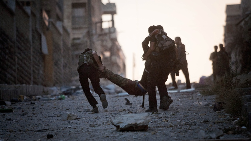 FSA soldiers help a severely wounded colleague after being shot by a Syrian Army sniper in Izaa district in Aleppo, Syria, Saturday, Sept 8, 2012. (AP / Manu Brabo)