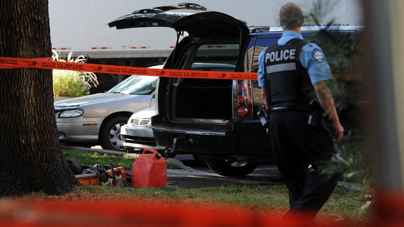 A police officer looks towards a black SUV that has had its contents removed at a crime scene outside the Metropolis in Montreal on Wednesday, September 5, 2012. (Sean Kilpatrick / THE CANADIAN PRESS)