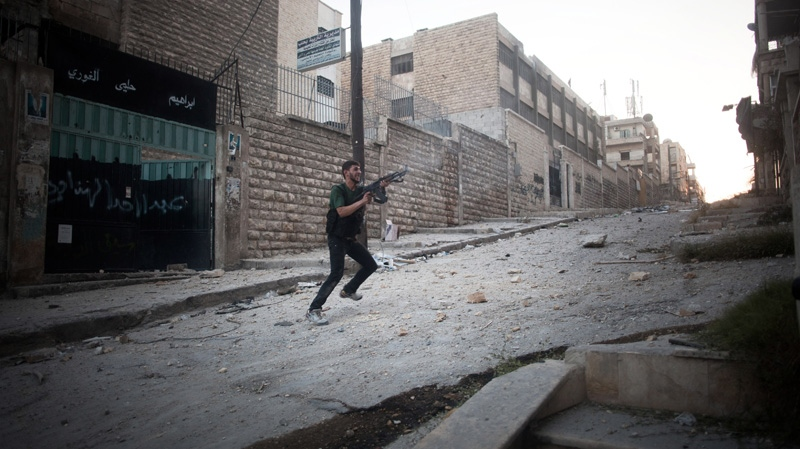 An FSA soldier fires his weapon towards Syrian Army positions in the Izaa district in Aleppo, Syria, Saturday, Sept 8, 2012. (AP /  Manu Brabo)