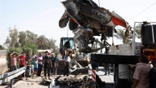 A destroyed car is moved from the scene of a car bomb attack in the town of Taji, about 20 kilometre