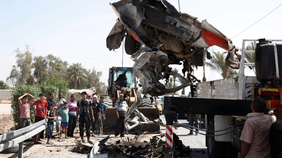 A destroyed car is moved from the scene of a car bomb attack in the town of Taji, about 20 kilometres north of Baghdad, Iraq on Sunday, Sept. 9, 2012. (AP /Karim Kadim)