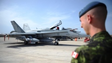 A Canadian soldier looks at a CF-18 as it sits loaded for flight at Camp Fortin on the Trapani-Birgi
