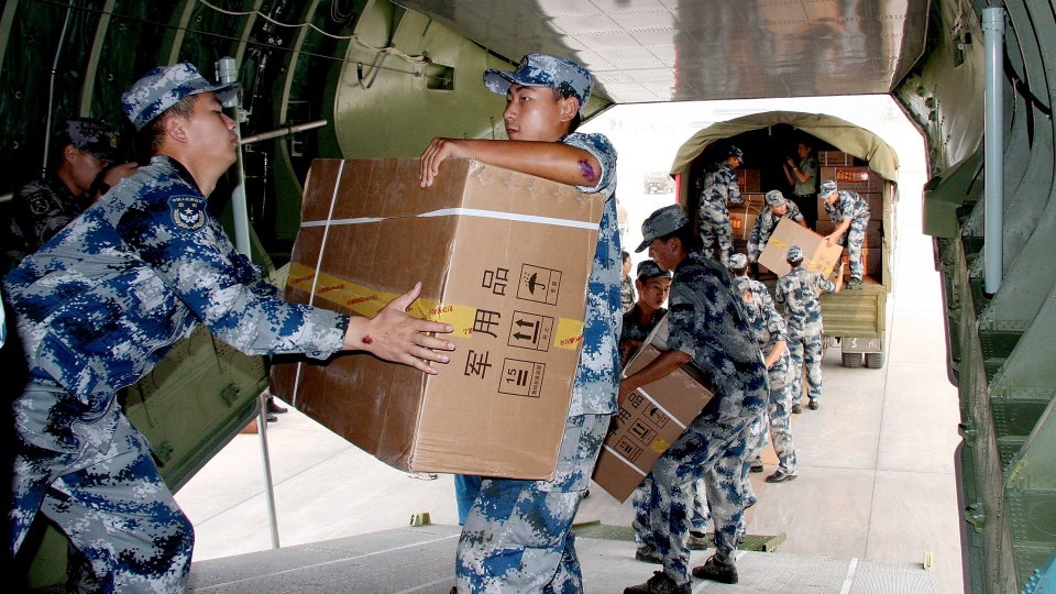 Chinese soldiers load relief materials into a military aircraft bound for Zhaotong, which was struck by Friday's earthquakes, in Yunnan province at an airport in Chengdu in southwest China's Sichuan province on Sunday, Sept. 9, 2012. (AP Photo)