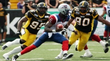Alouettes quarterback Adrian McPherson tries to escape pressure by Tiger-Cats Justin Hickman (left) and Demonte Bolden during first half CFL action in Hamilton, Ont., Saturday, September 11, 2010. (THE CANADIAN PRESS/Dave Chidley)