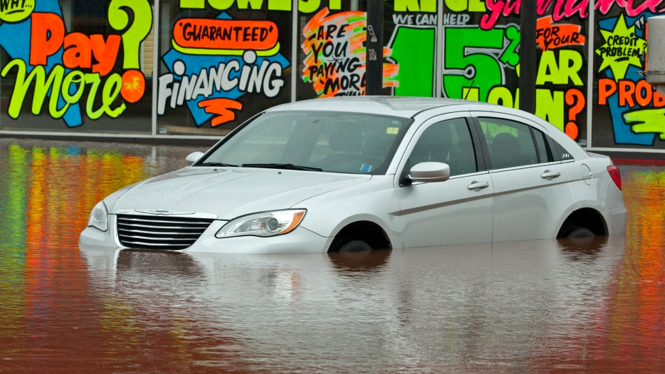 A vehicle sits outside a car dealership as dikes on the Salmon River gave way in Truro, N.S. on Monday, Sept. 10, 2012. (Andrew Vaughan / THE CANADIAN PRESS)