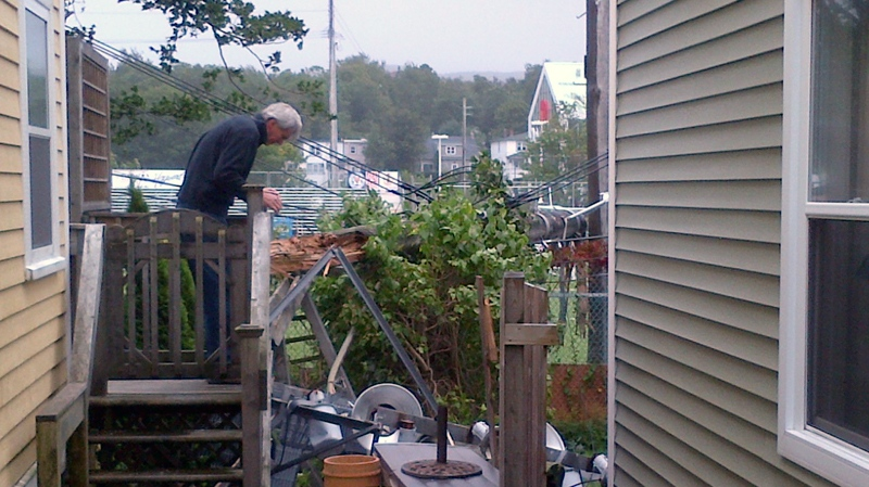A homeowner inspects damage after a tower pole with stadium lights came down on his house in St. John's, N.L., Tuesday, Sept. 11, 2012. (Todd Battis / CTV News)
