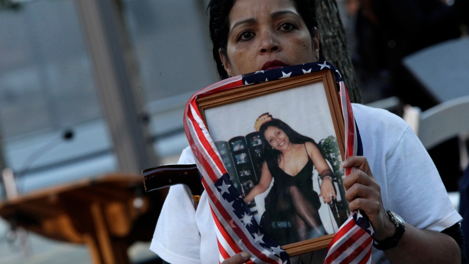 Linda Torrens holds a portrait of her cousin Janine Nicole Gonzalez during the observances held on the eleventh anniversary of the attacks on the World Trade Center, Tuesday, Sept. 11, 2012 in New York. (AP / Mary Altaffer