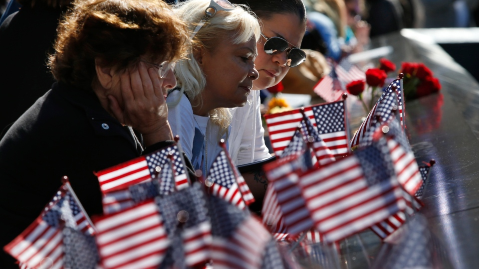 Rema Weiser, Virginia Pacheco and Dinah Pacheco, left to right, pause at the edge of the north reflecting pool of the World Trade Center Memorial during ceremonies marking the 11th anniversary of the Sept. 11 attacks, in New York, Tuesday, Sept. 11 2012. (AP / Mike Segar)