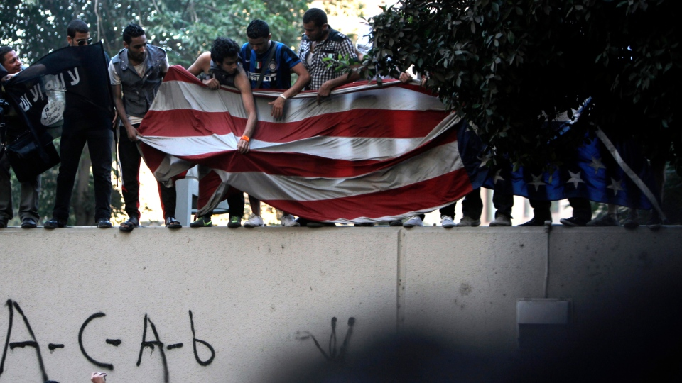Protesters carry an American flag pulled down from the U.S. embassy in Cairo, Egypt on Tuesday, Sept. 11, 2012. (AP /Nasser Nasser)