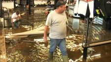 People are seen walking through a flooded sporting goods store in Truro, N.S. on Tuesday, Sept. 11,