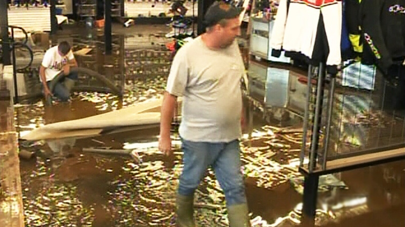 People are seen walking through a flooded sporting goods store in Truro, N.S. on Tuesday, Sept. 11, 2012.