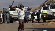 A miner dances in front of police near S. Africa's Lonmin Platinum Mine on Sept. 11, 2012.