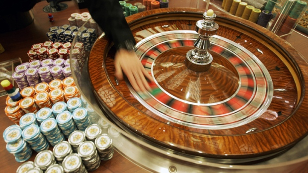 A staff member demonstrates the roulette wheel at Grand Lisboa Casino in Macau on Feb. 11, 2007.