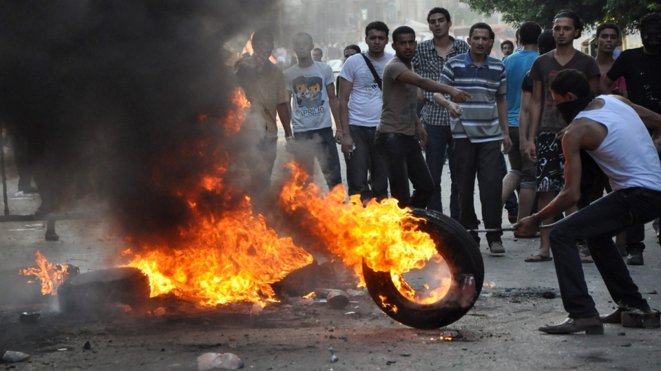 Egyptian protesters burn tires as they clash with riot police, unseen, outside the U.S. embassy in Cairo, Egypt, early Thursday, Sept. 13, 2012, as part of widespread anger across the Muslim world about a film ridiculing Islam's Prophet Muhammad. (AP / Hussein Tallal)
