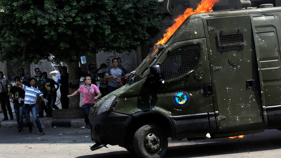 Egyptian protesters throw stones at a riot police armored vehicle that was hit by a fire bomb during clashes outside the U.S. embassy in Cairo, Egypt, Thursday, Sept. 13, 2012. (AP / Nasser Nasser)