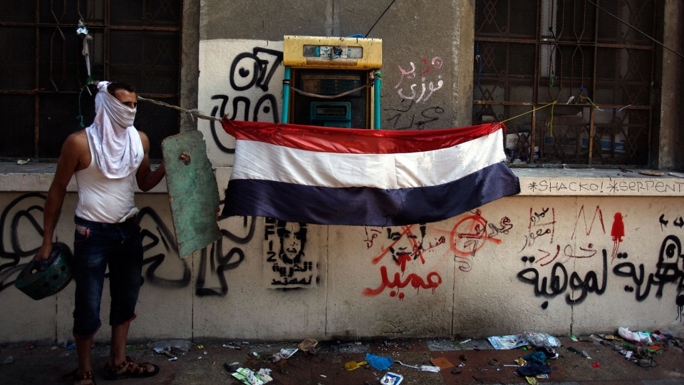 An Egyptian protester stands next to a national flag during clashes near the U.S. embassy in Cairo, Egypt, Thursday, Sept. 13, 2012. (AP/Khalil Hamra)