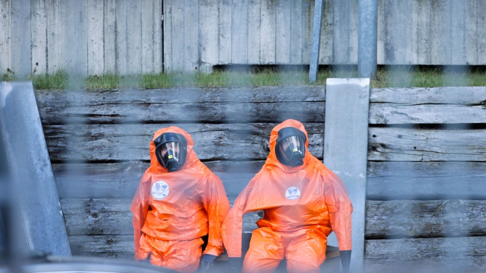 Workers in protective clothing sit in the courtyard of the U.S. consulate in Berlin, Thursday, Sept. 13, 2012. The U.S. Embassy says its consulate in Berlin has been evacuated as a precaution after an employee reported a strange smell from an envelope. (AP/Markus Schreiber)