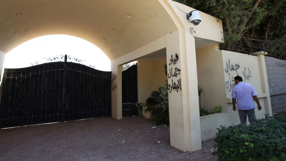A Libyan man walks past by the U.S. consulate's main gate, after an attack that killed four Americans, including Ambassador Chris Stevens on the night of Tuesday, Sept. 11, 2012, in Benghazi, Libya. (AP/Mohammad Hannon)