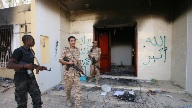 Libyan military guards check one of the U.S. Consulate's burnt out buildings during a visit by Libya
