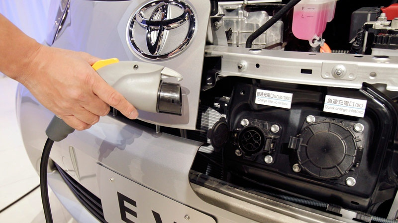 A journalist holds a battery recharging plug for Toyota's electric vehicle.  (AP Photo/Koji Sasahara)