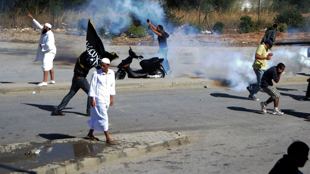 "Demonstrators throw stones during a protest against the anti-Islam film ""Innocence of Muslims"" outside the U.S. Embassy in Tunis, Tunisia, as police respond with tear gas Friday, Sept. 14, 2012. (AP Photo/Hassene Dridi)"