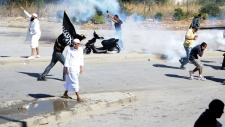 Demonstrators protest outside the US embassy , unseen, in Tunis, Friday, Sept.14, 2012 as police res