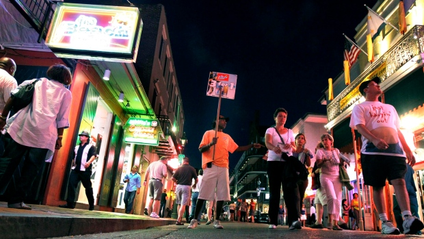 Frank Singleton holds a sign promoting three-for-one drinks on Bourbon Street in the French Quarter