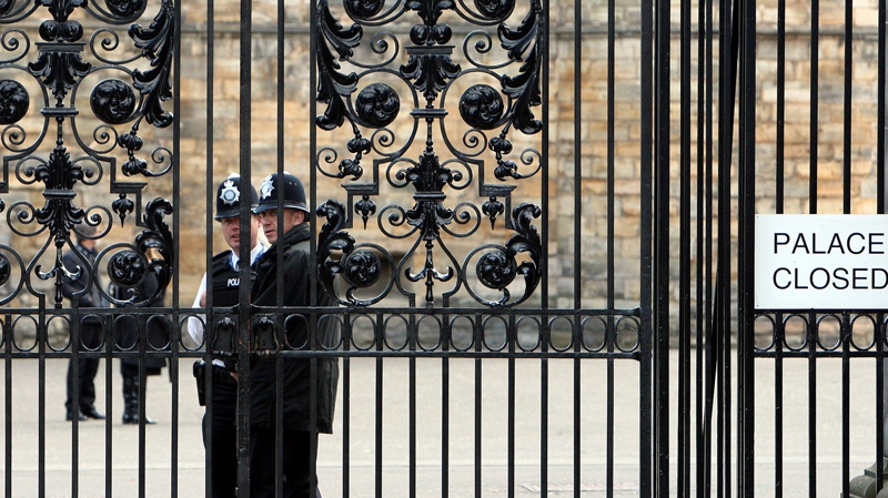 Police officer's are seen behind the closed gates of Holyrood Palace, Edinburgh, Scotland, Wednesday Sept. 15, 2010. Pope Benedict XVI arrives on Thursday for a four-day visit, the first-ever state visit by a Pope to Britain. (AP / Scott Heppell)