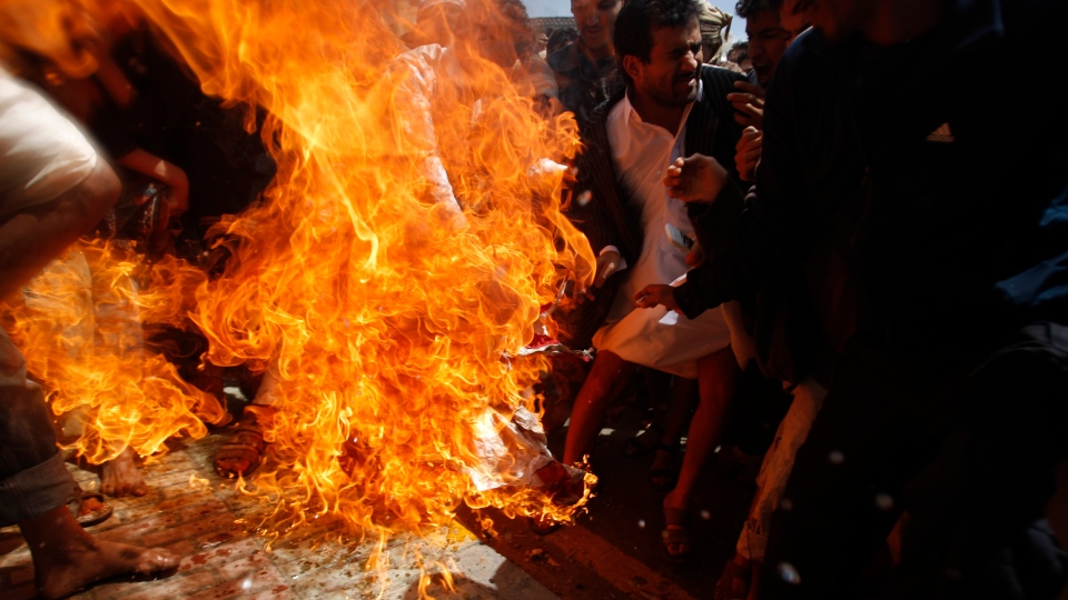Protesters burn an American flag during clashes with police near the U.S. Embassy in Sanaa, Yemen, Friday, Sept. 14, 2012. (AP / Hani Mohammed)