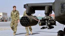 Prince Harry, left, is shown the Apache helicopter by a member of his squadron