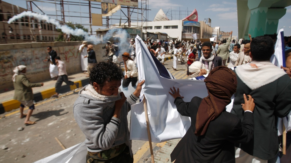 Protesters run from tear gas released by riot police during clashes near the U.S. Embassy in Sanaa, Yemen, Friday, Sept. 14, 2012. (AP / Hani Mohammed)