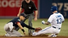 Toronto Blue Jays' Brett Lawrie is tagged at second base by Boston Red Sox short stop Jose Iglesias under the watchful eye of second base umpire Brian Gorman during first inning AL action in Toronto on Friday September 14, 2012. (Frank Gunn / THE CANADIAN PRESS)