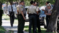 Los Angeles County sheriff's deputies stand down the street from a suburban Los Angeles