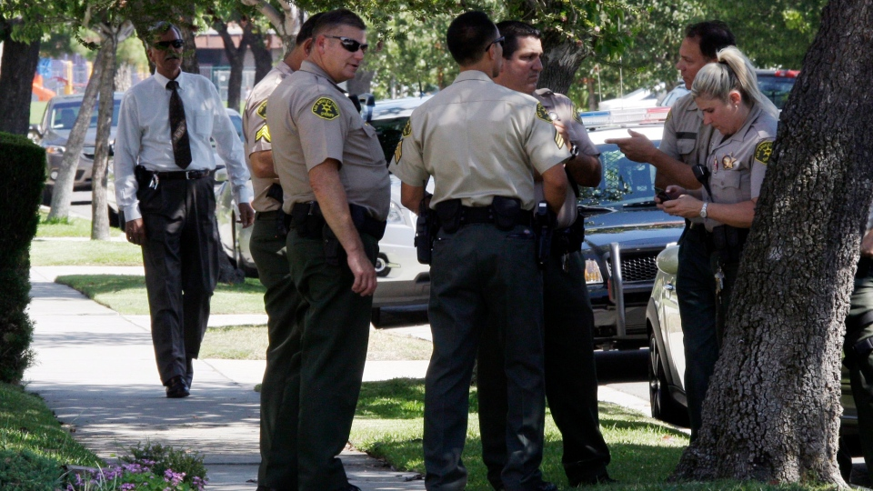 Los Angeles County sheriff's deputies stand down the street from a suburban Los Angeles home believed to be that of filmmaker Nakoula Basseley Nakoula, Friday, Sept. 14, 2012. (AP / Reed Saxon)