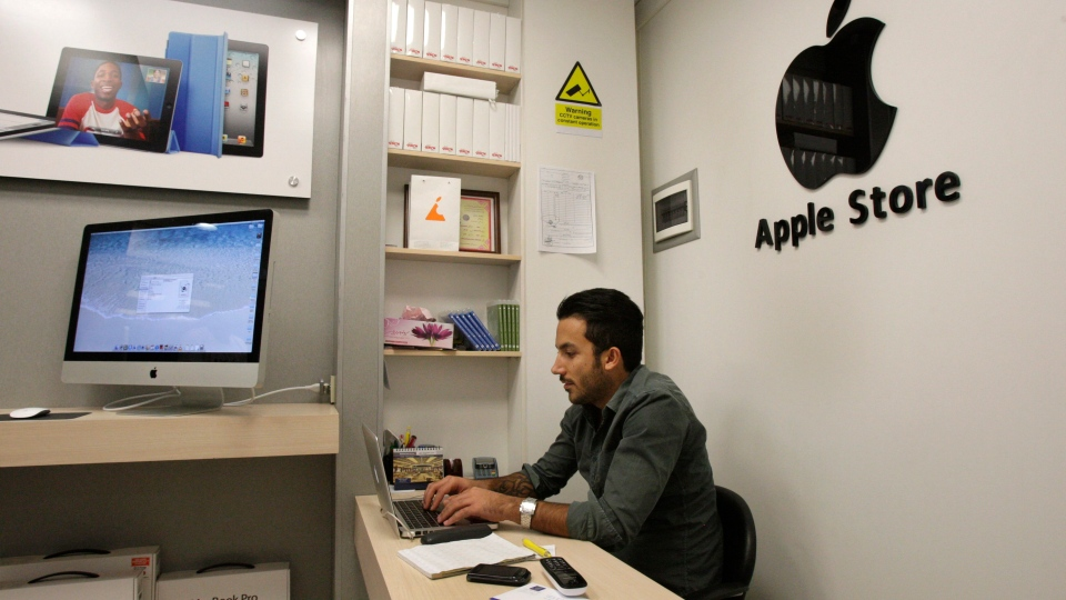 Iranian shopkeeper Amir Ali Beheshti, an Apple products seller, works on a lap top in his store, in an electronics market in northern Tehran, Iran on Saturday, Sept. 8, 2012.  (AP /Vahid Salemi)