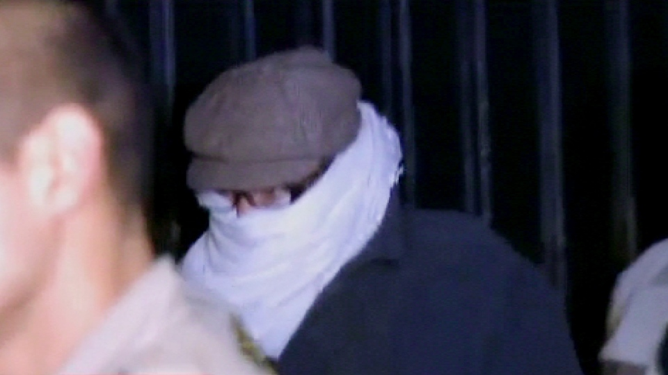 Nakoula Basseley Nakoula, the man behind the anti-Muslim movie that has inflamed the Middle East, is escorted by Los Angeles County sheriff's deputies from his home, in Cerritos, Calif., early Saturday, Sept. 15, 2012. (AP / CBS2-KCAL9)